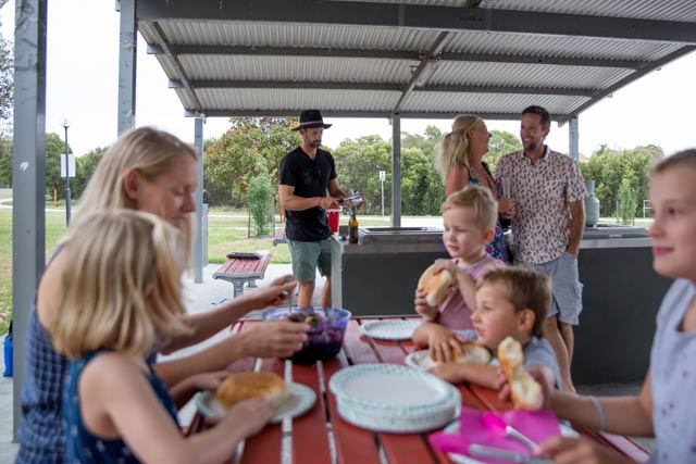 Family barbeque in the park using commercial barbeque equipment