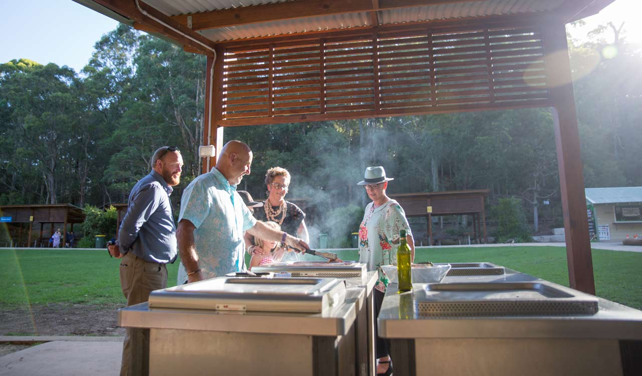 family using commercial bbq in the park